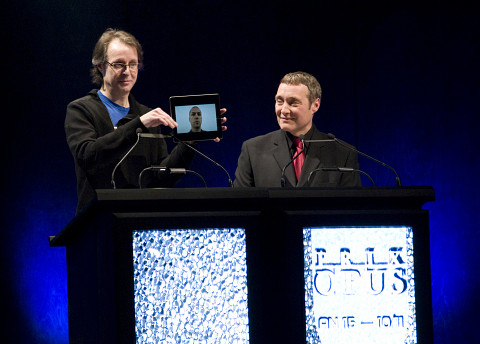 """Pierre Alexandre Tremblay (on the screen of an iPad held up by Jean-François Denis) receiving the Prix Opus 2010-11 """"Album of the year — actuelle and electroacoustic musics"""" at the 15th Gala des Prix Opus at Salle Bourgie in Montréal. The host of the event is Mario Paquet (on the right side) [Photo: CQM, Montréal (Québec), January 29, 2012]"""