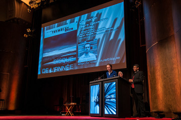 """Jean-François Denis is receiving (on behalf of Pierre Alexandre Tremblay visible on the big screen) the Prix Opus 2013-14 """"Album of the year — actuelle and electroacoustic musics"""" at the 18th Gala des Prix Opus at Salle Bourgie in Montréal. The hosts of the event are Pierre Vachon and Stanley Péan [Photo: Anis Hammoud — CQM, Montréal (Québec), February 1, 2015]"""